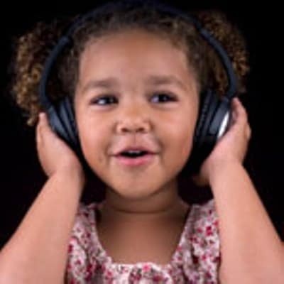 A cute female child listening song with headphone and she is singing too.