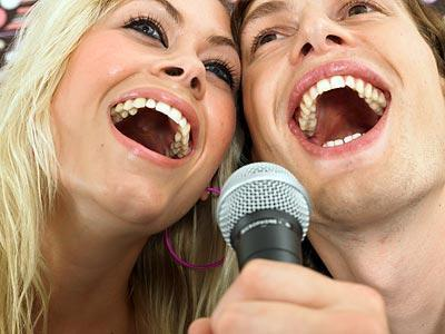 A pair of boy and girl are singing happily in a singing room.