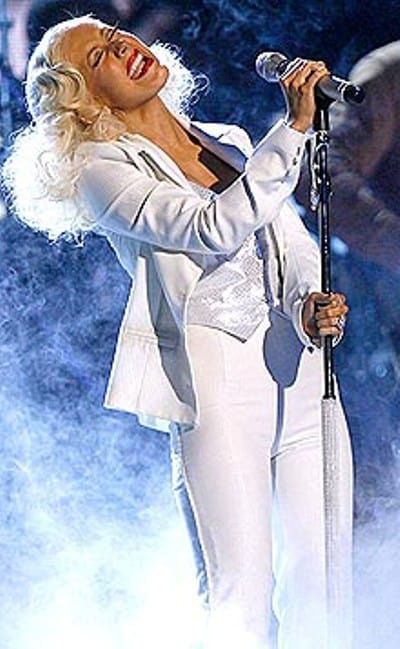 Christina with white suit performs songs on the stage of Annual Grammy Awards.