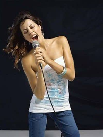The girl vocal training and practise singing herself in a small room.