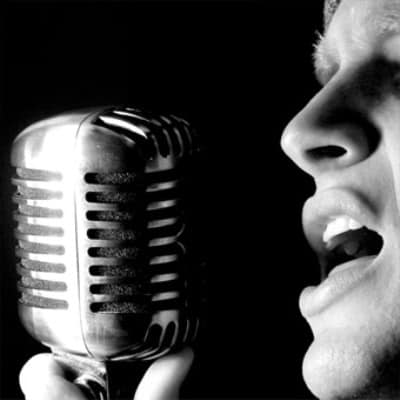 The professioal vibrato male singer sings a vibrato song with microphone.
