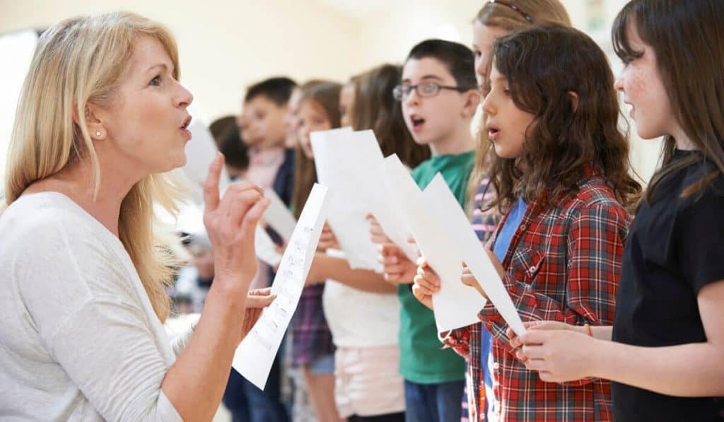 Teacher teach children how to sing properly.