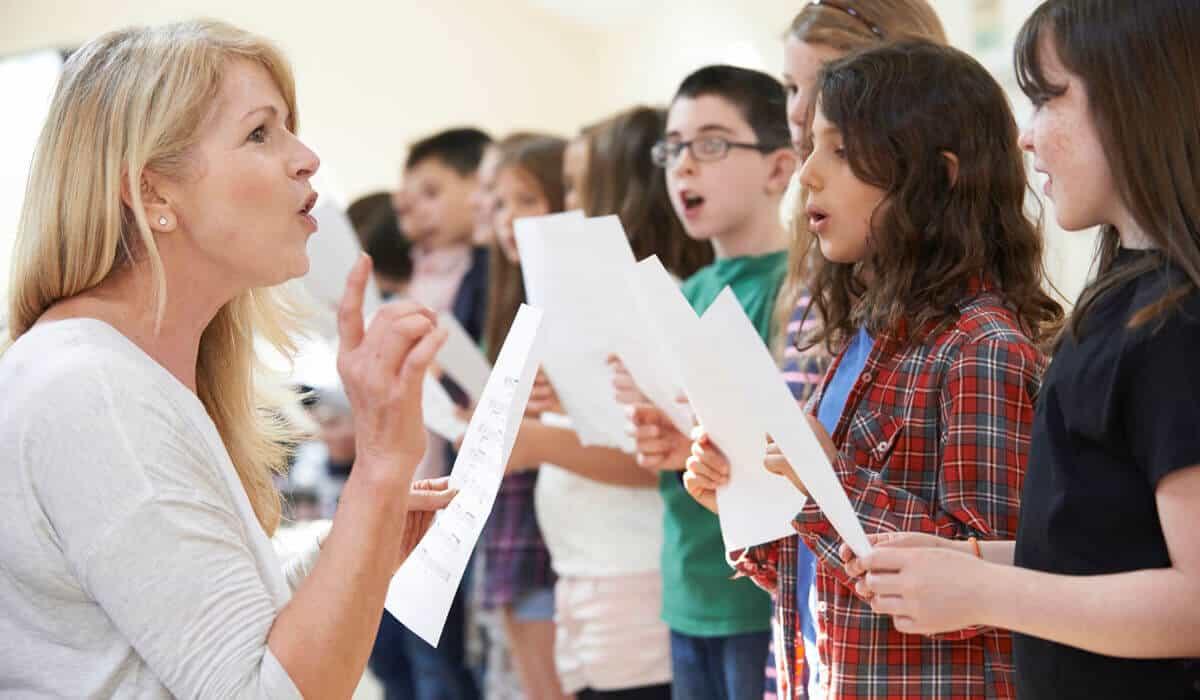 Teacher teach children how to sing properly.