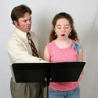 Vocal coach is teaching student how to sing.