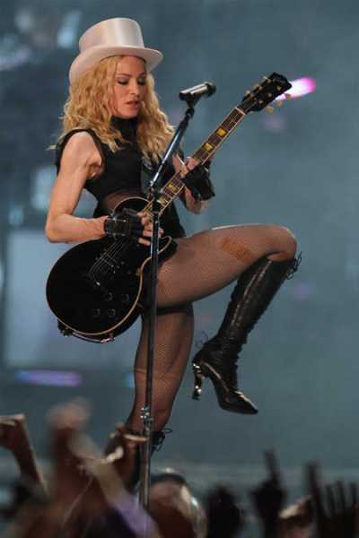 Wearing top hat sexy Madonna playing guitar on the stage in France.