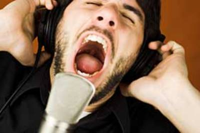 Man sings and screams the high notes with the microphone at the music studio.