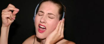 Singer train her voice with headphones on.