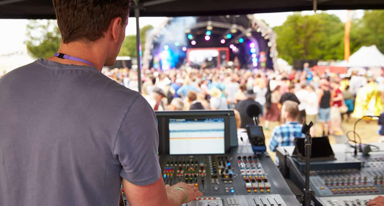 Sound engineer is monitoring the sound outputs in the live concert.