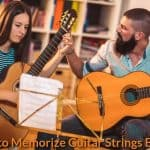 A guitar teacher is teaching a student.
