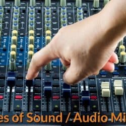 DJ adjusting the knobs of audio mixer.