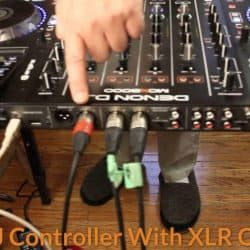 The audio engineer is pointing to the XLR cable outputs of a DJ controller.