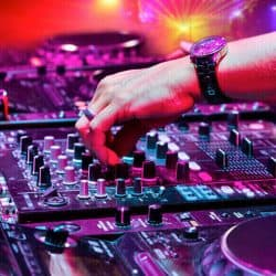 DJ is adjusting the knobs and levers of the Dj controller mixer.