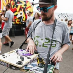 DJ is scratching on the portable DJ turntable while walking on the street.