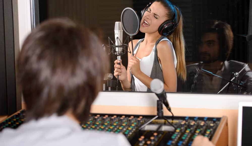 Producer is recording a singer's vocal in studio.