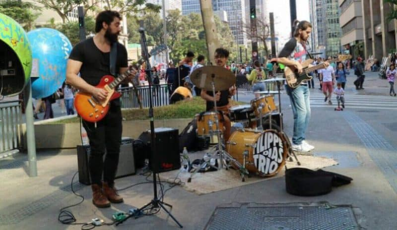 A band busking on the street with a PA system.