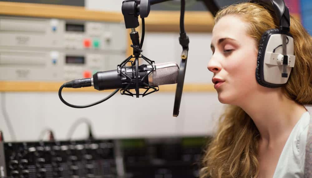 A female singer is recording vocal tracks in the studio.