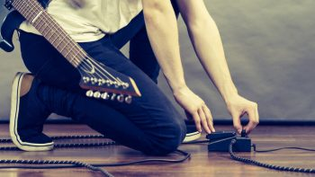 Guitar player configure and setting the loop pedal on the floor.