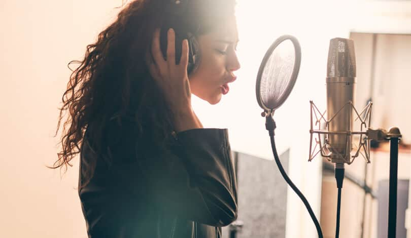 Singer recording vocal tracks in home studio.