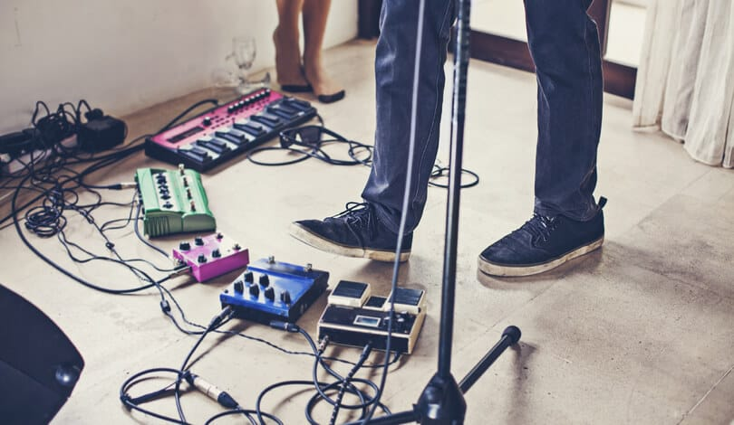 Singer make music and write song using loop pedals.